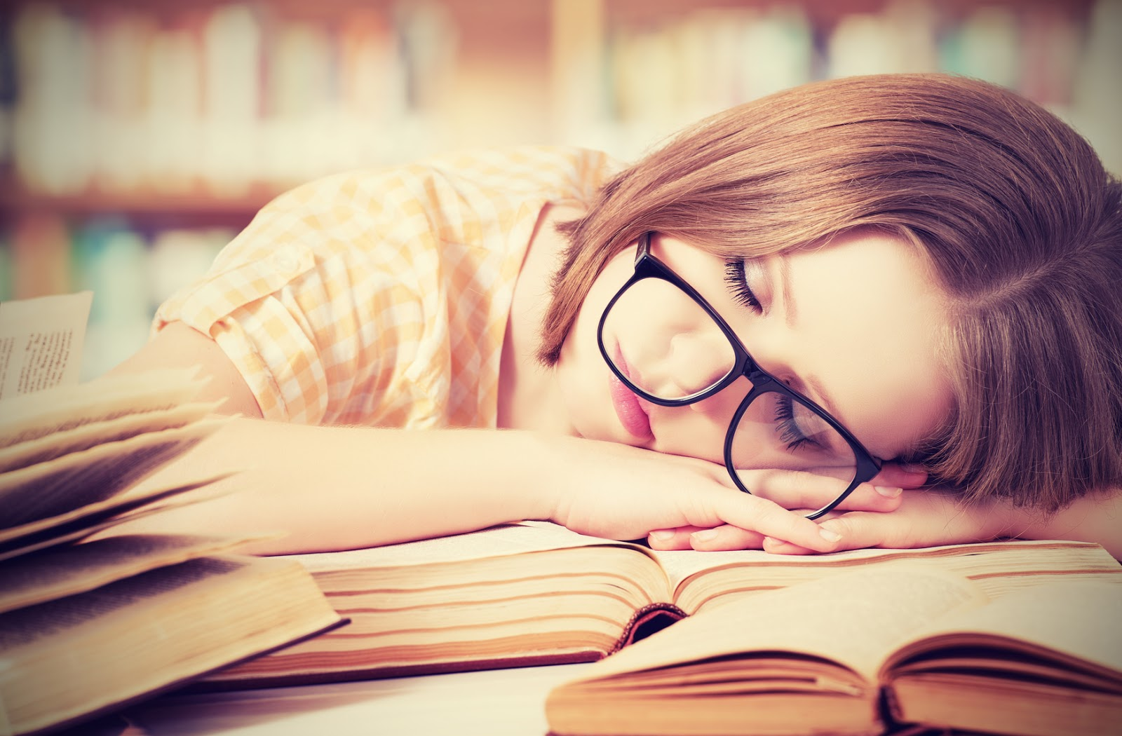 طالبة نائمة فوق الكتب